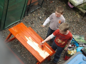 Boys weather-proofing the picnic bench